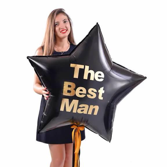 Большая черная звезда с золотой надписью The Вest Man и декором золотыми и черными лентами
