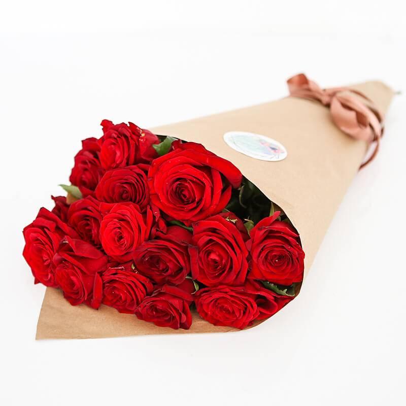 Букет из 15 алых роз в крафт бумаге